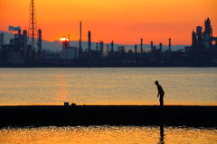 Angler and sunset of factory Stock Images