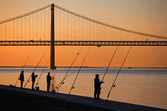 Angler at the Tagus river. Angler silhouettes at the Tagus river in Lisbon, Portugal royalty free stock photo
