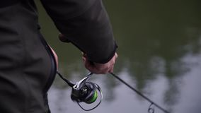 Angler twists spinning reel and catch trout stock video footage