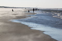 Angler and walkers upon beach in Nes, Ameland, Holland Stock Photography