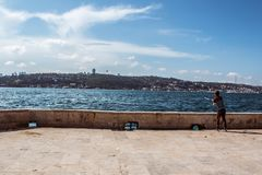 Angler young man is fishing at Beylerbeyi Seashore, Bosphorus, Blue Sky. Angler Man is fishing at Beylerbeyi Seashore, Bosphorus. Blue Sky. Beylerbeyi is located stock photo