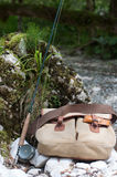 Anglers bag with a rod. Fly fishing rod and a bag on the bank of mountan river Stock Image