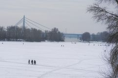 Anglers with equipment are fishing on the river Dnipro on ice in winter day. Fishermen. Kyiv, Ukraine.  Stock Image