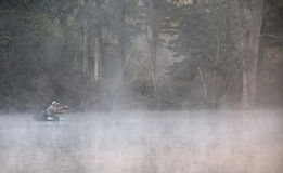 Anglers fishing on a Lake. Anglers enjoy a beautiful, fishing from their small fishing boat on a sunlit lake Stock Images