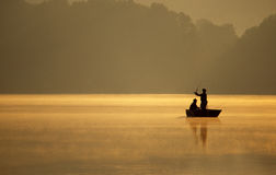 Anglers Fishing on a Lake. A pair of anglers enjoy a beautiful, golden, misty morning fishing from their small fishing boat on a sunlit lake stock photography