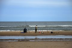 Anglers fishing by the sea. St Cyrus, Aberdeenshire, Scotland stock image