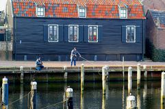 Anglers are fishing in the traditional fishing village Spakenburg, Netherlands. Anglers are fishing in the traditional fishing village Spakenburg with wooden Royalty Free Stock Image