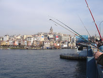 Anglers at Galata Bridge. Pera and Galata Tower behind fishing rods of anglers at Galata Bridge over the Golden Horn, Istanbul Royalty Free Stock Image