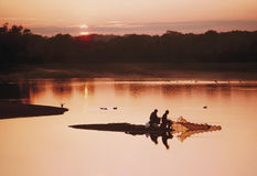 Anglers at sunset. Atmospheric water scene with two anglers fishing at a tranquil lake as the sun sets over the water Stock Image