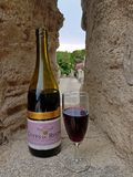 Angles/France - 06.15.2017: a bottle and a glass of wine from the southern region Cote du Rone on a wall of Stones. royalty free stock photography