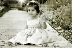 Anglic baby. Photo of a baby girl sitting on a path with wings Royalty Free Stock Photography
