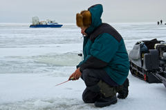 Angling. Man catches fish on ice, and the background is seen the boat amphibious hovercraft Stock Photos