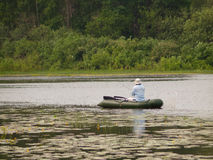 Angling fisherman in a boat. Fisherman with tackle in rubber boat on the river Royalty Free Stock Photography
