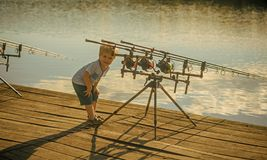 Angling, fishing, activity, adventure, hobby, sport. Angling child with fishing rod on wooden pier royalty free stock image