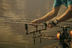 Angling, hobby, sport, activity, recreation. Rods, reels, lines and male hands on water background fishing Fishing equipment gear device stock image