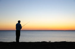 Angling man by sunset. Silhouette of an angling man by a colorful sunset Royalty Free Stock Photos