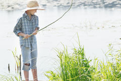 Angling teenage boy looking at handmade green twig fishing rod in his arms Royalty Free Stock Photo