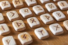 Anglo-saxon wooden handmade runes on the vintage table On each rune symbol for fortune telling is designated.  royalty free stock photography