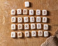 Anglo-saxon wooden handmade runes on the vintage table On each rune symbol for fortune telling is designated.  royalty free stock photo