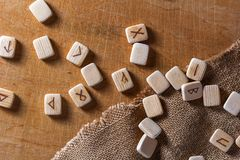 Anglo-saxon wooden handmade runes on the vintage table On each rune symbol for fortune telling is designated.  stock images
