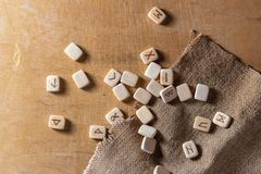 Anglo-saxon wooden handmade runes on the vintage table On each rune symbol for fortune telling is designated.  royalty free stock image
