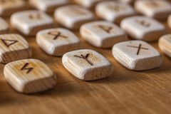 Anglo-saxon wooden handmade runes on the vintage table On each rune symbol for fortune telling is designated.  stock photography