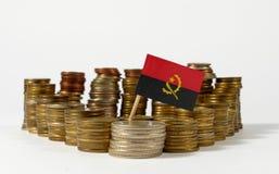 Angola flagga med bunten av pengarmynt Royaltyfri Bild