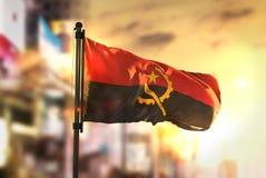 Angola flagga mot suddig bakgrund för stad på soluppgångpanelljuset Royaltyfria Foton