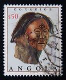 Angola-Stempel zeigt lederne Maske mit gemalter Dekoration Stockfotos