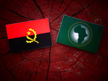 Angolan flag with African Union flag on a tree stump. Angolan flag with African Union flag on a tree stump Royalty Free Stock Photography