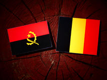Angolan flag with Belgian flag on a tree stump isolated Royalty Free Stock Photos