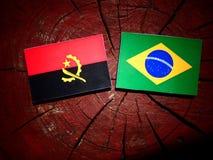 Angolan flag with Brazilian flag on a tree stump isolated Stock Photo
