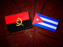 Angolan flag with Cuban flag on a tree stump isolated Stock Image
