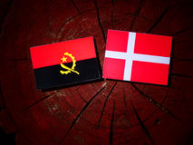 Angolan flag with Danish flag on a tree stump isolated Stock Photos