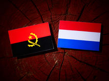 Angolan flag with Dutch flag on a tree stump isolated. Angolan flag with Dutch flag on a tree stump Stock Photography