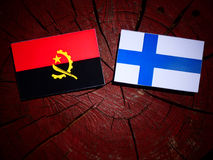 Angolan flag with Finnish flag on a tree stump isolated. Angolan flag with Finnish flag on a tree stump Royalty Free Stock Photo