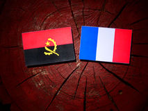 Angolan flag with French flag on a tree stump isolated. Angolan flag with French flag on a tree stump Royalty Free Stock Images