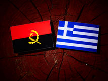 Angolan flag with Greek flag on a tree stump isolated Stock Photo