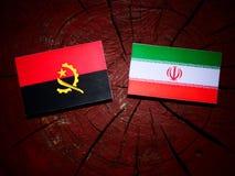 Angolan flag with Iranian flag on a tree stump isolated Stock Image