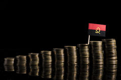 Angolan flag with lot of coins isolated on black Royalty Free Stock Photo