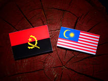 Angolan flag with Malaysian flag on a tree stump isolated Royalty Free Stock Photography