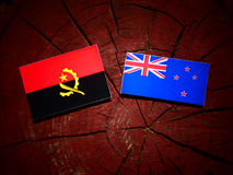 Angolan flag with New Zealand flag on a tree stump isolated Royalty Free Stock Photo
