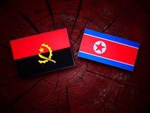Angolan flag with North Korean flag on a tree stump  Stock Photos