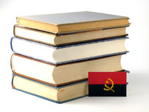 Angolan flag with pile of books  on white background Royalty Free Stock Photography