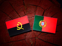 Angolan flag with Portuguese flag on a tree stump isolated. Angolan flag with Portuguese flag on a tree stump Royalty Free Stock Photography