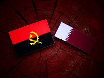 Angolan flag with Qatari flag on a tree stump isolated. Angolan flag with Qatari flag on a tree stump Royalty Free Stock Photography