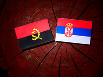 Angolan flag with Serbian flag on a tree stump isolated Stock Image
