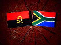 Angolan flag with South African flag on a tree stump isolated. Angolan flag with South African flag on a tree stump Stock Photography
