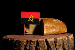 Angolan flag on a stump with bread.  Stock Images