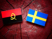 Angolan flag with Swedish flag on a tree stump. Angolan flag with Swedish flag on a tree stump Stock Images